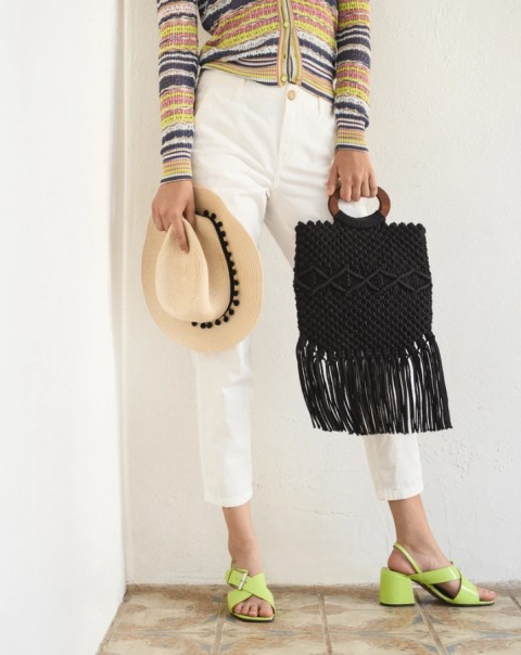 With striped button down shirt, white cropped pants, hat and green low heeled shoes