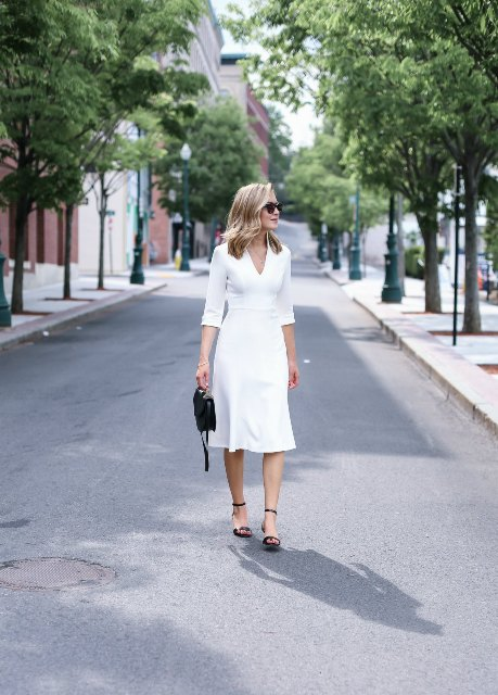 With white V-neck midi dress and black mini bag