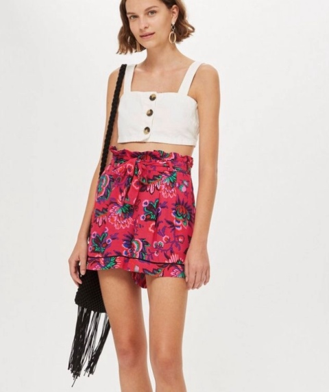 With white crop top and black fringe bag