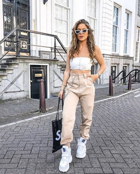 With white crop top, sunglasses, white platform sneakers and tote bag