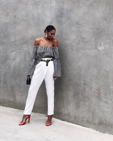 With white high waisted trousers, black bag and red shoes