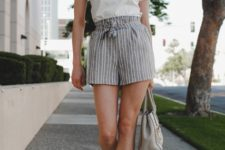 With white labeled t-shirt, gray bag and black flat mules