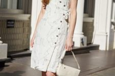 With white leather bag and black sandals