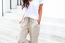 With white loose t-shirt, beige hat and beige flat sandals
