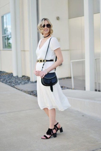 With white midi dress, black belt and black embellished bag