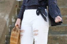 With white pants and straw bag