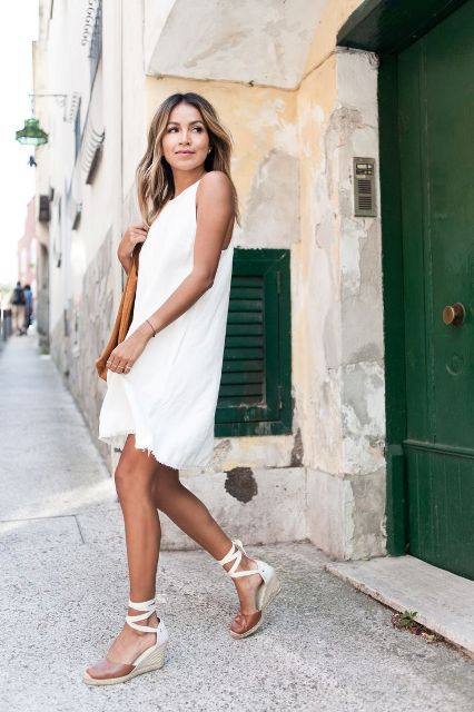 With white sleeveless dress and bag