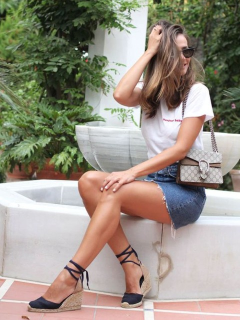 With white t-shirt, denim skirt and printed bag