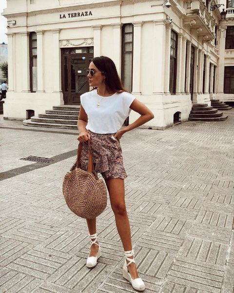 With white t shirt, leopard ruffle mini skirt and rounded bag