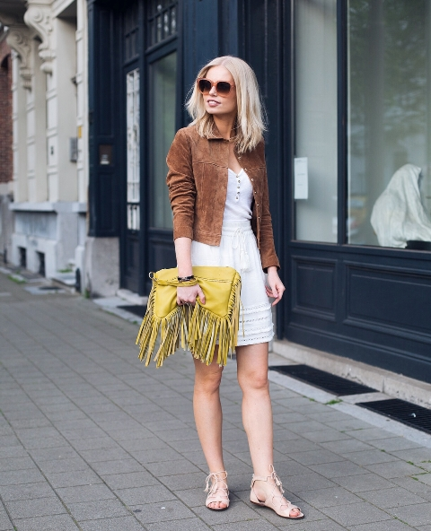 With white top, brown suede jacket, beige mini skirt and flat shoes