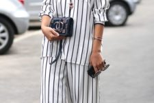 a black and white pajamas suit, a statement necklace, a black crossbody bag and sunglasses