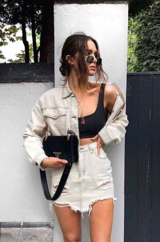 a black bra crop top, a white ripped denim skirt and a matching cropped denim jacket, a black bag