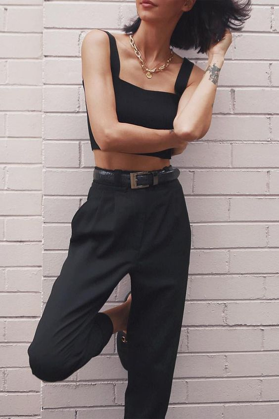 a black bra crop top, black pants, black mules and a statement chain necklace for a chic look