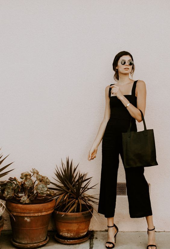 a black fitting jumpsuit with thick straps and cropped pants, black minimalist heels and a black tote
