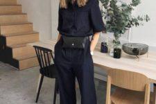 a black linen jumpsuit, a black waist bag and black sporty sandals for a minimalist work look