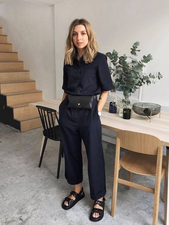 a black linen jumpsuit, a black waist bag and black sporty sandals for a minimalist work look