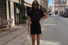 a black mini dress with a high neckline and short sleeves, black sporty sandals and a white bag