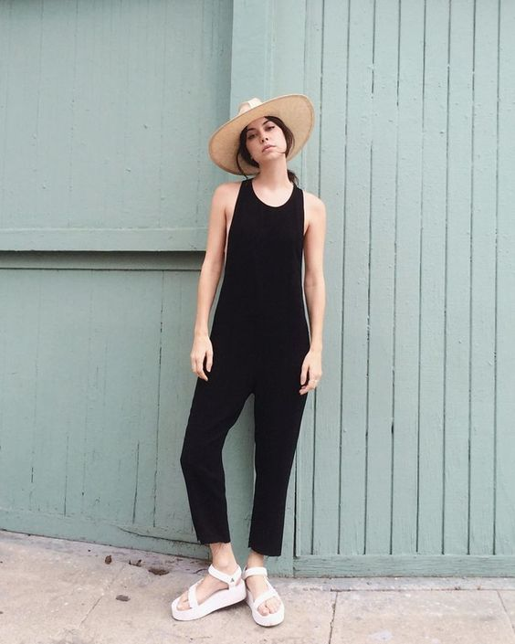 a black plain jumpsuit, white sporty sandals and a hat for a stylish and bold summer look