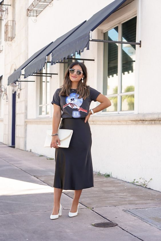 a black printed tee, a black satin midi, white shoes and a white clutch and statement earrings