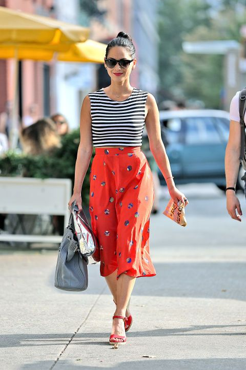 a bold look with a striped sleeveless top, a red printed midi, red heels and a silver clutch