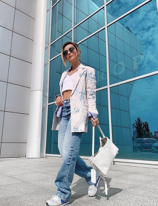 a bold look with blue baggy jeans, a white crop top, a floral oversized blazer and a white bag