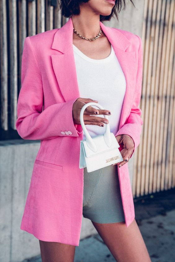a bold summer look with a white top, grey shorts, a hot pink blazer and a small white bag
