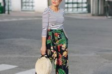 a bright outfit with a striped top, tropical print trousers, yellow block heels and a wicker bag