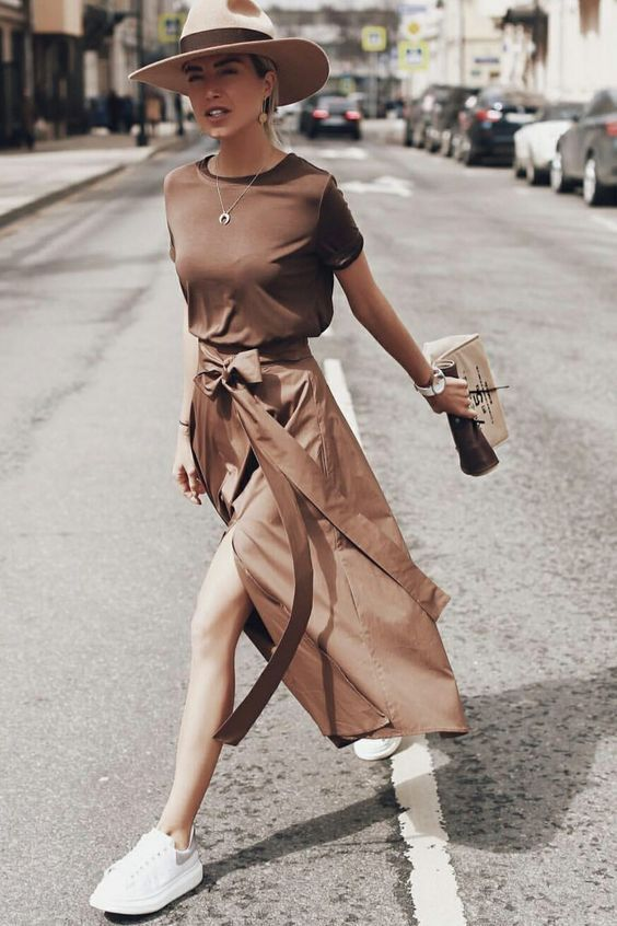 a brown t shirt, a matching asymmetrical midi skirt, white sneakers and a hat