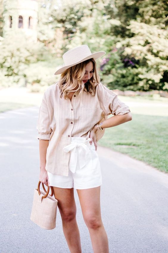 a casual summer look with a tan striped shirt with cuffed sleeves, white paper bag shorts, a neutral bag and a boater hat