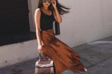 a chic look with a black tank top, a rust-colored satin midi, a brown bag and matching slingbacks