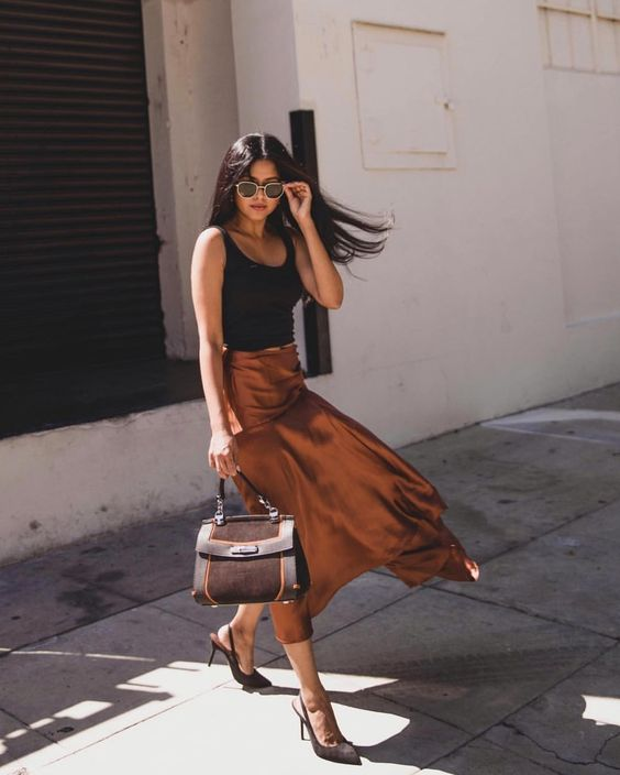 a chic look with a black tank top, a rust colored satin midi, a brown bag and matching slingbacks