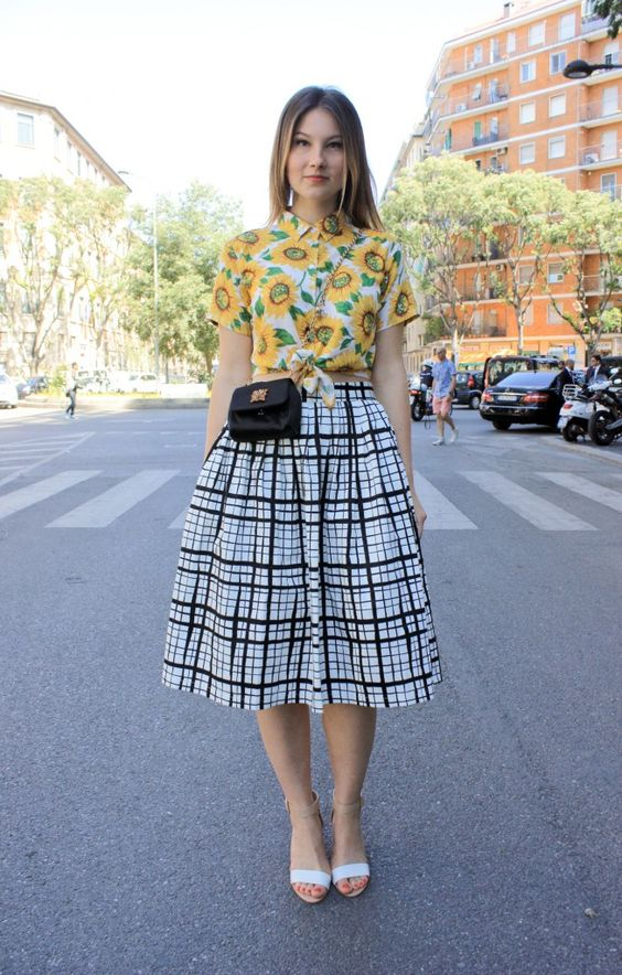 a chic outfit with a bright sunflower print crop shirt, a plaid full skirt, two tone heels and a black bag