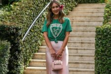 a colorful look with a green printed t-shirt, a pink satin midi, pink heels and a blush bag