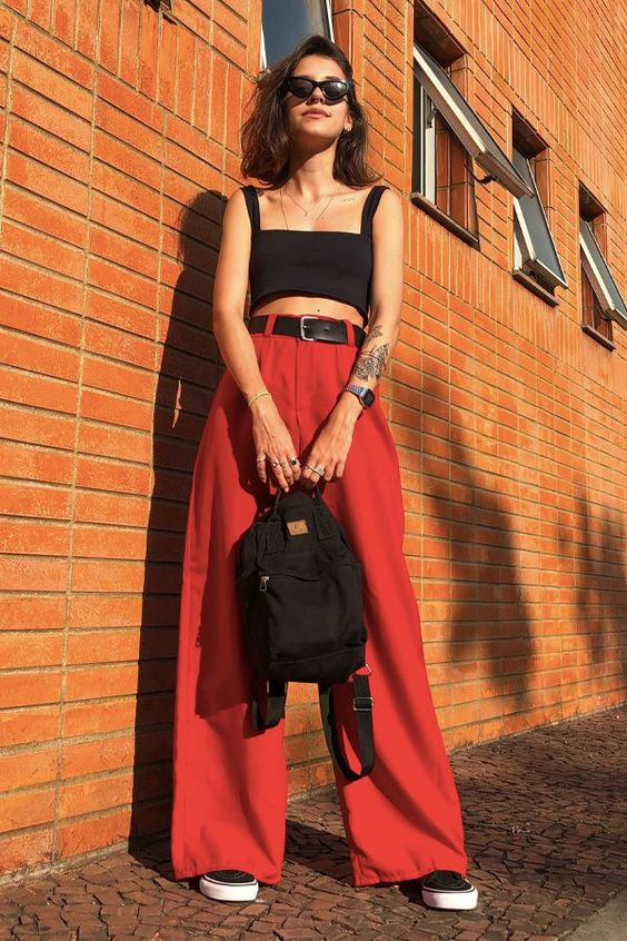 a contrasting look with a black bra crop top, red high waisted wideleg pants, black sneakers and a backpack