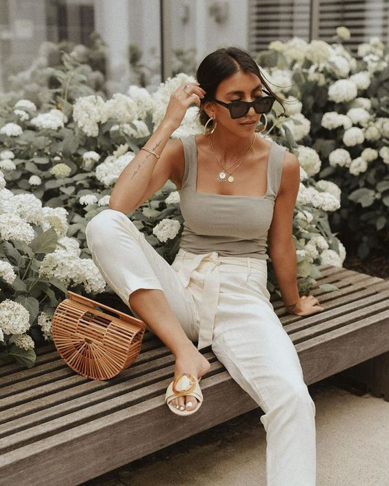 a dove grey top with a square cut, white paperbag pants, neutral embellished slippers and a wooden bag