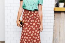 a green floral tee, a burgundy floral midi, red heels and a small clutch for a party