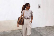 a grey tied up tee, neutral high waisted pants, brown suede trainers and a large tote