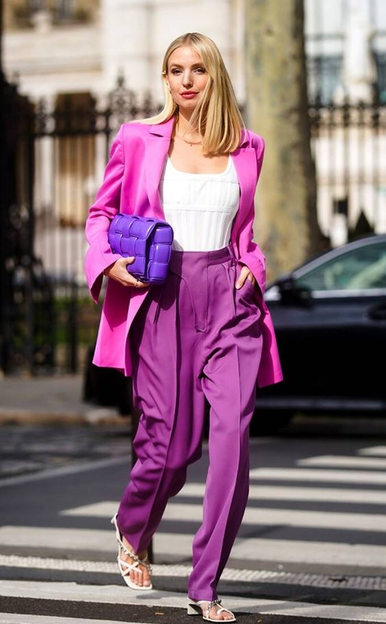 a hot pink blazer, purple pants, a white top, a hot purple bag and white square toe shoes