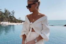 a light vacation look with an off the shoulder tied crop tp and shorts plus a statement necklace