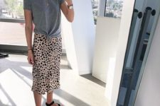 a modern everyday outfit with a grey tied up tee, leopard print midi, blakc sporty sandals and a necklace