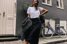 a monochromatic look with a white tee, a black satin midi, black trainers and a black tote