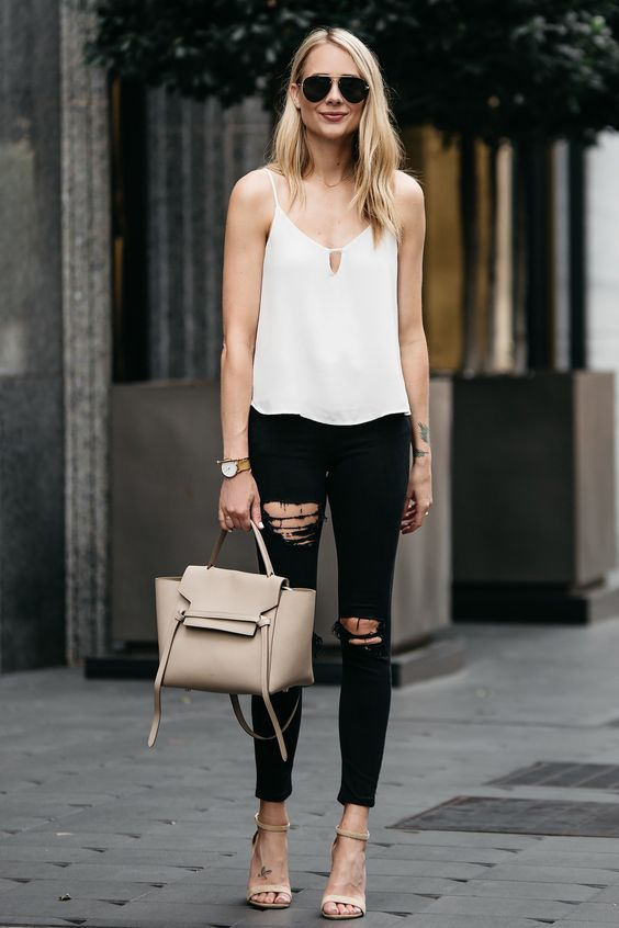 a monochromatic outfit with a white spaghetti strap top, black ripped jeans, tan minimalist heels and a neutrla tote