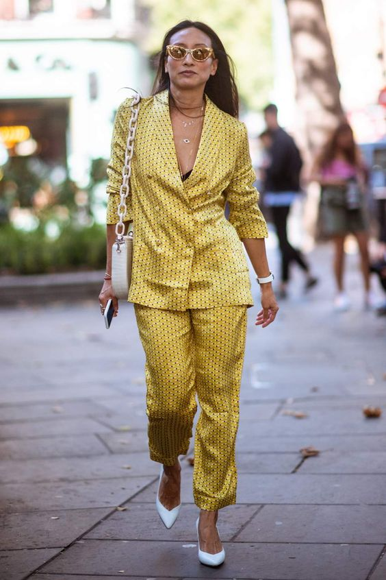 a mustard printed pajamas suit, white shoes and a white bag on chain for a wow look