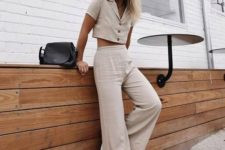 a neutral linen suit with a button up crop top, wideleg pants, checked slipons and a black saddle bag