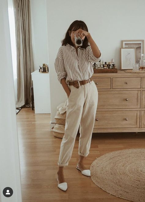 a neutral striped shirt with long sleeves, white linen pants, white flats and a brown belt