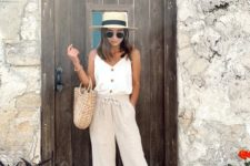 a neutral vacation look with a white button up top, linen pants, gilded flats, a straw hat and a bag