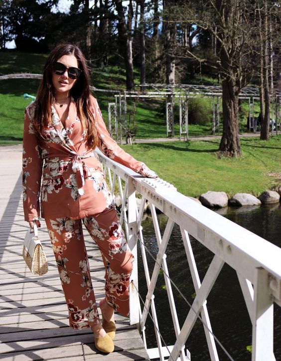 a pink floral pajamas suit with cropped pants, mustard suede mules and a wicker bag