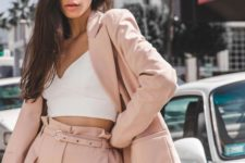 a pink shorts suit with an oversized long blazer and paperbag shorts plus a white bra crop top