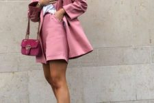 a pink suit with shorts, a white t-shirt, colorful trainers and a hot pink velvet bag
