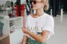 a printed tee, a green wrap floral skirt and layered necklaces for a summer feel in your look